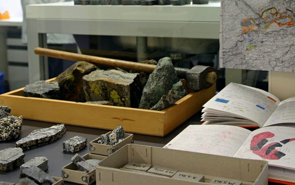 Hammer, field book and hand specimens of rock